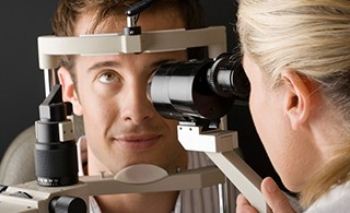 Doctor looking at eye with slit lamp